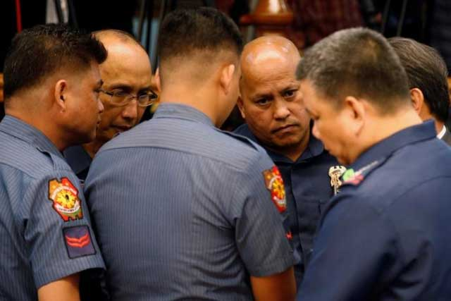 Philippine National Police chief Director-General Ronald dela Rosa (2nd-R) talks to fellow police officers during a Senate hearing regarding people killed during a crackdown on illegal drugs in Pasay, Metro Manila, Philippines August 23, 2016. REUTERS/Erik De Castro