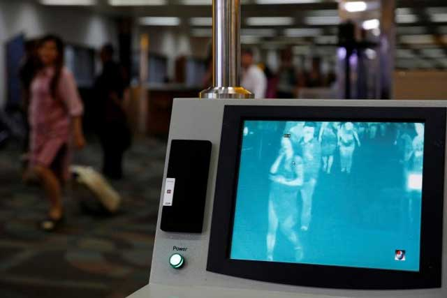Airplane passengers walks through feverscan camera system used to detect human temperature shortly after arriving from Singapore at the Soekarno-Hatta airport in Jakarta, Indonesia, August 30, 2016. REUTERS/Beawiharta