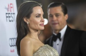 """Director and cast member Jolie poses, as her husband and co-star Pitt stands nearby, at the premiere of """"By the Sea"""" during the opening night of AFI FEST 2015 in Hollywood"""