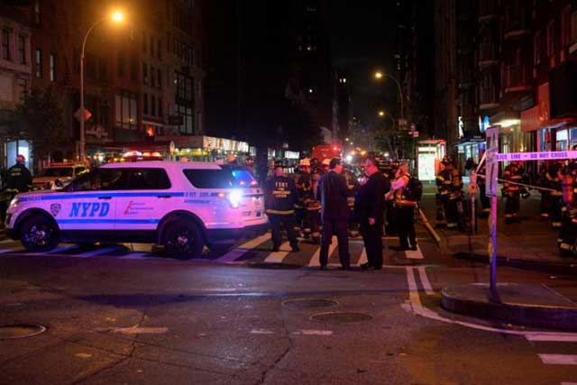 New York City police and firefighters stand near the site of an explosion in the Chelsea neighborhood of Manhattan, New York, U.S. September 17, 2016. REUTERS/Rashid Umar Abbasi