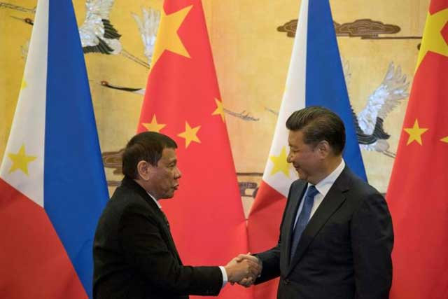 Philippine President Rodrigo Duterte (L) and Chinese President Xi Jinping shake hands after a signing ceremony held in Beijing, China October 20, 2016. REUTERS/Ng Han Guan/Pool