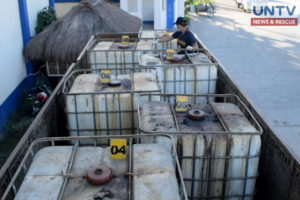 A police personnel inspects a truck loaded with hazardous chemical wastes at a checkpoint in Hermosa, Bataan.