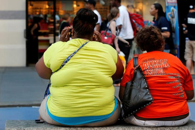 FILE PHOTO: Women sit on a bench in New York's Times Square May 31, 2012. REUTERS/Brendan McDermid