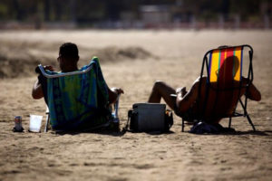 FILE PHOTO: Men lay out in the sun during warm weather at Orchard Beach in the Bronx borough of New York, U.S., October 19, 2016. REUTERS/Shannon Stapleton