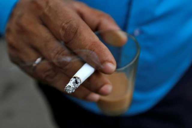 A man smokes a cigarette along a road in Mumbai, India, October 26, 2016. REUTERS/Danish Siddiqui/File Photo