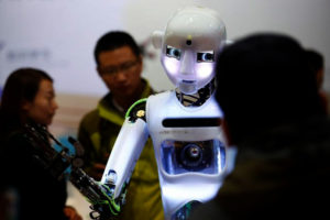 FILE PHOTO: People look at a RoboThespian humanoid robot at the Tami Intelligence Technology stall at the WRC 2016 World Robot Conference in Beijing, China, October 21, 2016. REUTERS/Thomas/File Photo