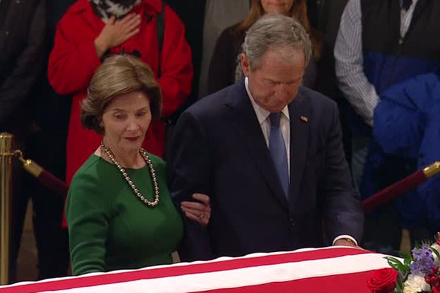 Former US President George W. Bush and former First Lady Laura Bush silently standing at his father's flag-draped casket | REUTERS