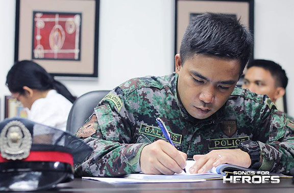 A representative from the AFP jots down notes during a meeting of the Songs for Heroes 2 organizers.