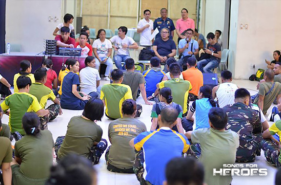 The production team of Songs for Heroes 2 meets with the performers from the AFP and PNP during one of the concert's rehearsals.