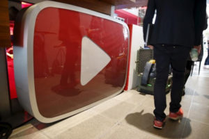 A man walks past a YouTube logo at the YouTube Space LA in Playa Del Rey, Los Angeles, California, United States October 21, 2015. REUTERS/Lucy Nicholson